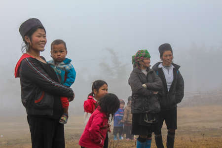 Sapa, Vietnam - January 16th 2014: Hmong people and the children on a cold, misty morning in Sapa, Vietnam