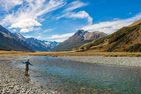 A fly fisherman casting for trout, surrounded by snow capped mountains, on the Ahuriri River, South Island, New Zealand
