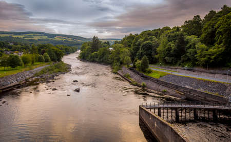 A view down the River Tummel at sunset from Pitlochry dam, on a cloudy summers evening in Pitlochry, Scotland