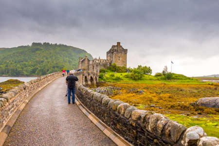 Eilean Donan, Scotland - July 14th 2016: Tourists walking on the bridge to Eilean Donan Castle, on a cloudy evening in the Scottish Highlands