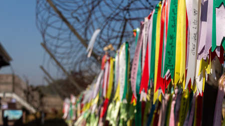 """Prayer ribbons attached to a barb wire fence at the Korean Demilitarized Zone, South Korea. Translation: """"Peace"""""""
