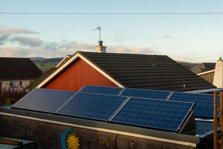 Solar panels generating electricity on a roof in low sun light in winter in scotland, United Kingdom Stockfoto