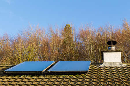 Solar panels generating electricity on a roof in low winter sunlight, Scotland, United Kingdom