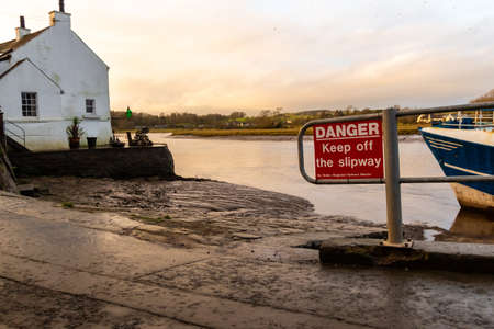 Danger Keep off the slipway sign at Kirkcudbright Harbour on a winters afternoon, Scotland