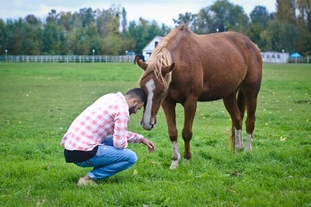 Young handsome guy Cowboy. man is a farmer in his ranch where there are many horses. Rural landscapes, countryside. Stock photos