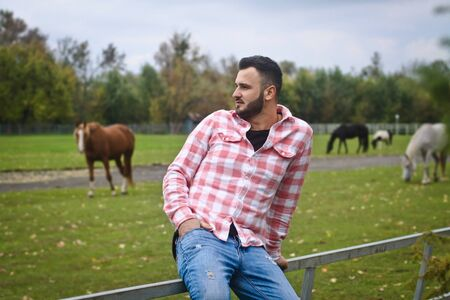 Young handsome guy Cowboy. A man is a farmer at his ranch near the fence. Rural landscapes, countryside. Trees, field, farm. Stock photos