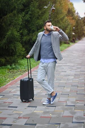 Fashionably dressed guy is traveling with luggage in the background of a road and trees. The man hurries on his flight and pours coffee, tea. Stock photo for design
