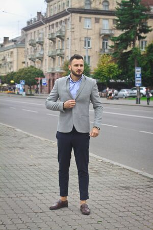 Portrait of a businessman on the street near the road of a European city. A bearded handsome man dressed stylishly. Fashionable guy hipster. Stock photos