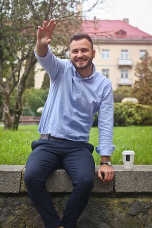 Portrait of a guy in a shirt sitting in a park in a European city. A man is greeted with other people against the background of trees and buildings. Stock photos