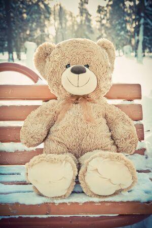 Christmas. Cute Teddy  bear on the bench silit with snow. Bear Reklamní fotografie