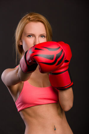 beautiful woman with the red boxing gloves, dark background photo