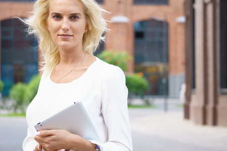 topicality: Happy business woman with tablet pc in front of office building Stock Photo