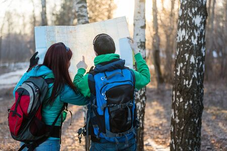 backpackers: Man and woman tourists backpackers reading map on trip. Young couple hikers looking at map. Stock Photo