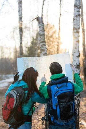 backpackers: Man and woman tourists backpackers reading map on trip. Stock Photo