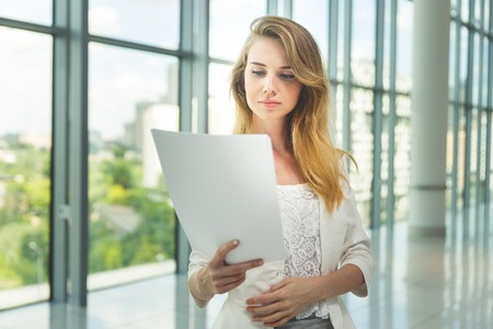 big window: Businesswoman hold some documents against a big window