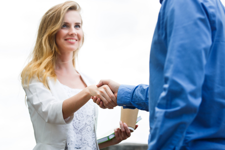 Dos personas, hombre y mujer dan apretón de manos después del acuerdo. Centrado en el apretón de manos Foto de archivo