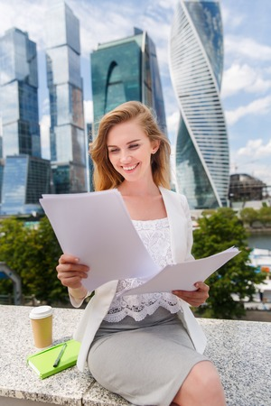 lawer: young smiling businesswoman with heap of papers sitting on city bench