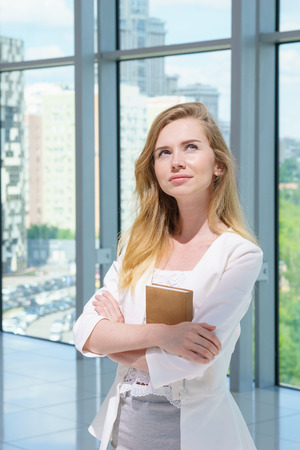 copybook: Beautiful businesswoman portrait with copybook in her hands.