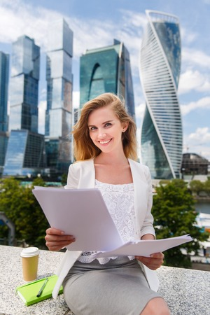 lawer: business, paperwork and people concept - young smiling businesswoman with heap of papers sitting on city bench Stock Photo
