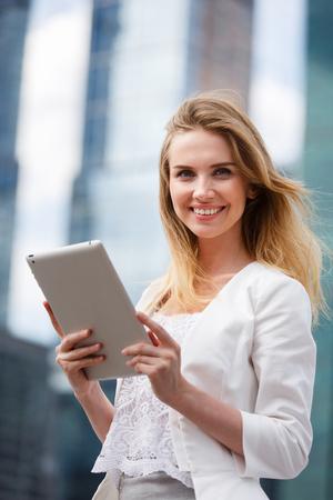 tab: Beautiful woman using electronic tab in the street