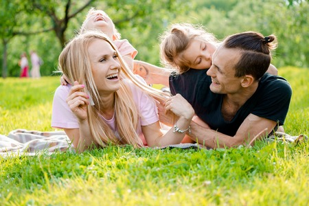 family tickle: Young big happy family lying on grass in countryside