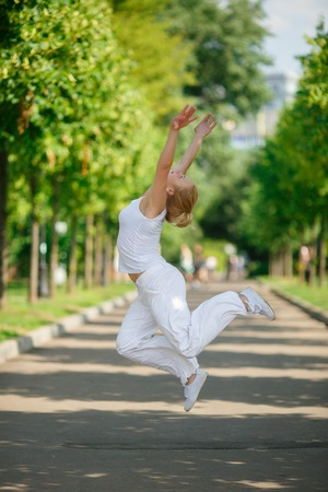 summer dress: Blonde girl in white dress jumping in summer sunny park