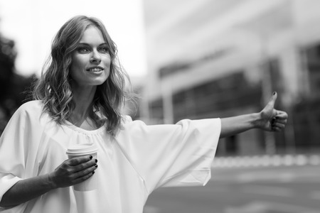 Black and white image of pretty woman stopping transport with thumb up Reklamní fotografie