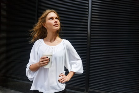 curiously: Portrait of dark background of young woman with waving blonde hair curiously looking up and holding coffee
