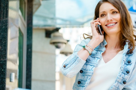 lady on phone: Happy caucasian young brunette lady talking on mobile phone outdoors