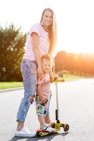 teaches: Beautiful girl teaches his son to ride a scooter.