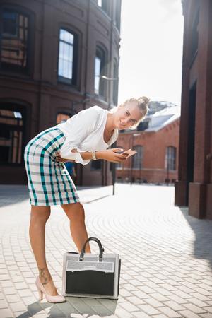 raises: beautiful young business woman raises the bag