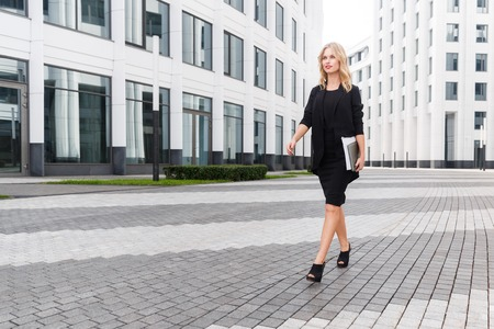striding: Beautiful business woman in black suit with laptop confidently striding across square