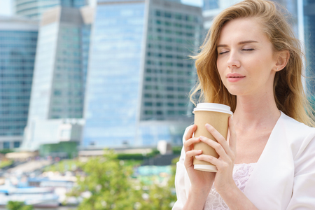 Cheerful business woman blonde holding coffee outdoors on city background Stock Photo