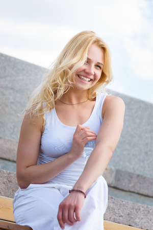 hot day: Happy young blonde woman in white dress resting outdoors with bottle of water on hot day