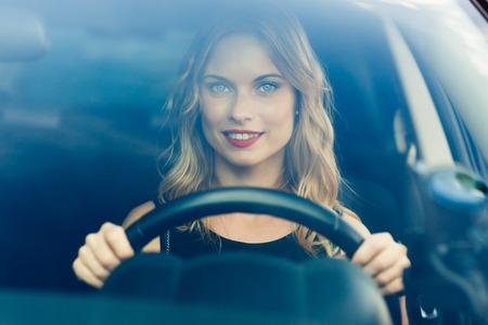 Portrait shot through windshield of blond pretty woman in car behind the wheel Banco de Imagens - 60726628