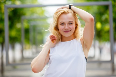 Beautiful young female touching her hair outdoors Stock Photo