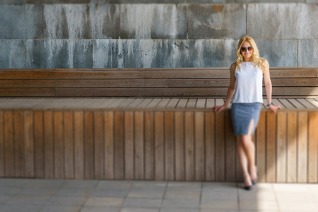 Caucasian young girl in summer clothes and sunglasses. Image with tilt-shift effect