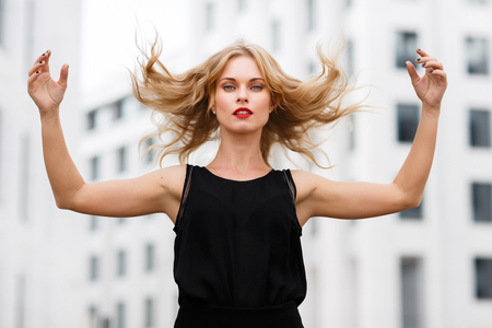 gesticulating: Outdoors portrait of young blond woman in motion, gesticulating with flying hair Stock Photo