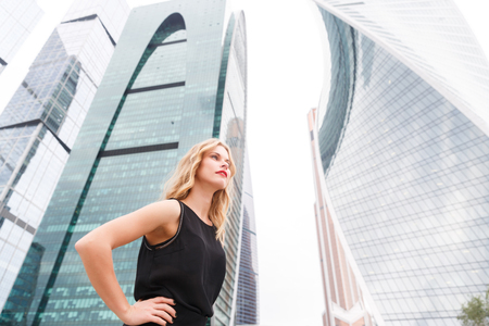 half turn: Businesswoman standing in half turn with hands on hips on street background