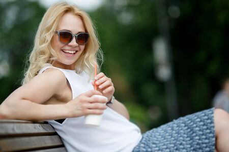Portrait of blond woman sitting on bench, holding milkshake and laughing. Image with tilt-shift effect
