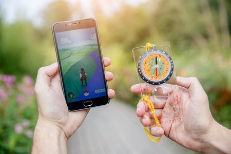 compas: Man held in hands compas and phone showing its screen with Pokemon Go application on forest background. Moscow, Russia. Editorial
