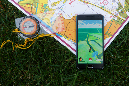Phone with Pokemon Go application on screen, maps and compas on grass. Moscow, Russia. Editorial