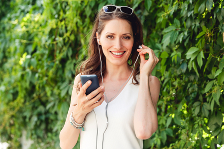 Beautiful brunette woman inserts earpiece into her ear and holding modern mobile phone