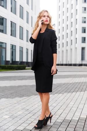 sidewalk talk: Portrait of elegant business lady in high heels in full-length talking on phone outdoors