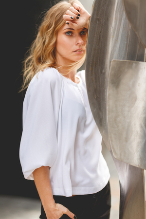 Outdoors portrait of pensive young blond woman with hand touching her forehead next to the sculpture