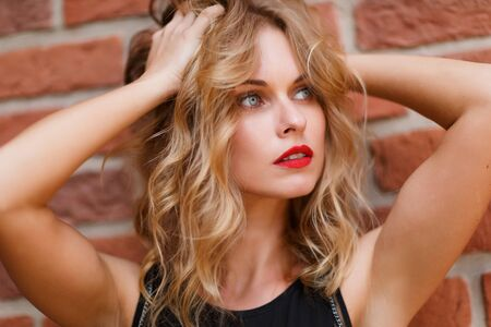 gray eyes: Beautiful blonde woman with natural make-up and gray eyes on brick background. Shoot on fast aperture