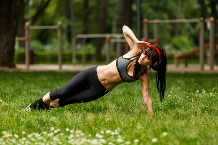 Slender strong woman in headphones and sportswear doing fitness exercises on grass nearly street gym