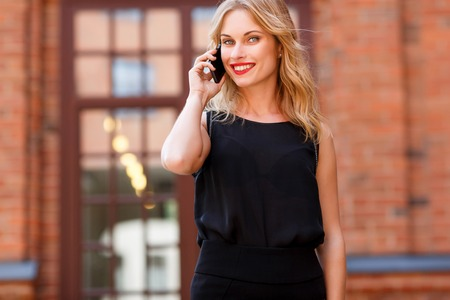 widely: Beautiful young business woman talking on mobile phone and smiling widely, portrait outdoors against the building