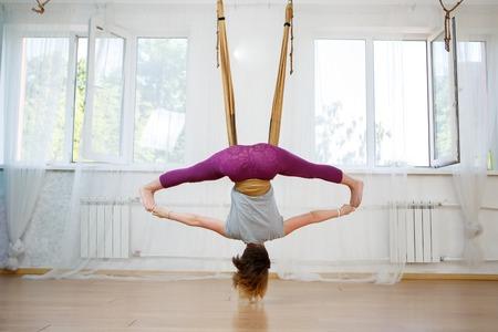 Young woman doing exercises of aerial yoga in hammock, model hanging upside down Banco de Imagens - 62532123