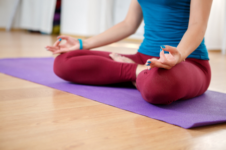 jnana: Young woman doing yoga at home, model sitting on mat in lotus position with hand in jnana mudra Stock Photo